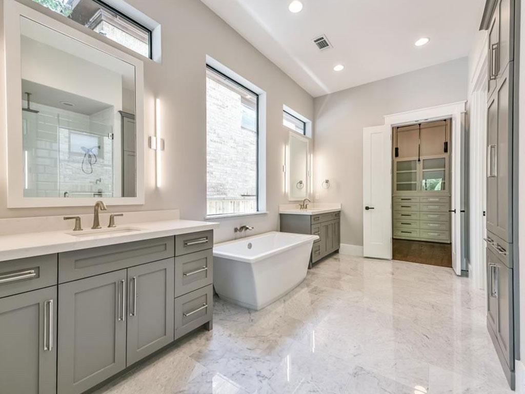 Luxurious bath offers soaking tub, seamless glass shower, separate vanities and custom lighting.