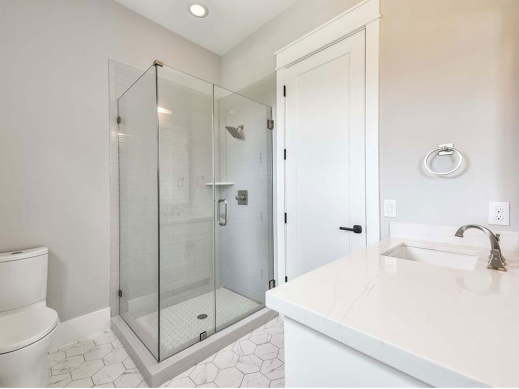 Sleek guest bath on the second floor with hexagon style flooring and seamless glass walk-in shower.