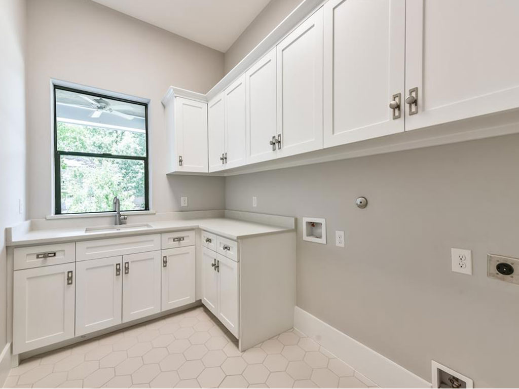 First floor utility room provides convenient storage space and sink.
