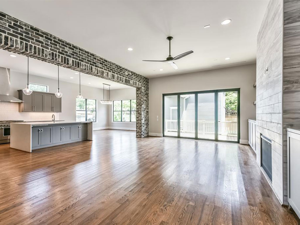 Another perspective of the open living area leading to the kitchen. Note the brick accents. Nano style doors lead out to the back porch.