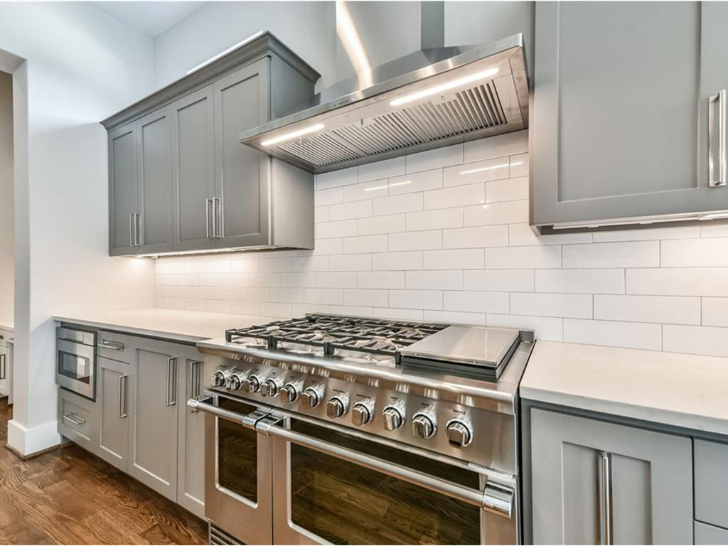 A closer view of the professional grade gas range and detailed subway tile backsplash.