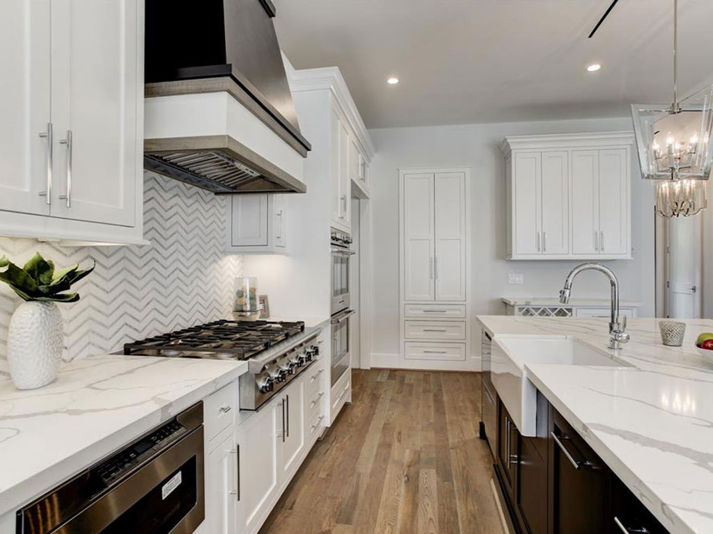 Six burner Fisher & Paykel gas cook top and white farmhouse sink. Richly appointed hardware and fixtures.